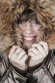 Young girl wearing winter coat warming herself — Stockfoto