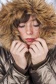Young girl wearing winter coat warming herself — Stock fotografie