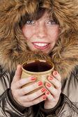 Young girl wearing winter coat warming herself — Stockfoto