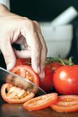 Chef Hand and Knife Slicing Tomato — Stock Photo