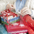Stockfoto: Man Concentrating On Gift Wrapping