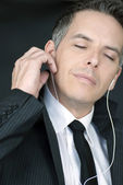 Serene Businessman Puts In Headphones — Stock Photo