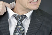Uncomfortable Businessman Pulls At Collar — Stock Photo