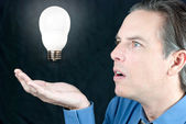 Businessman Looking At Floating Lightbulb — Stock Photo