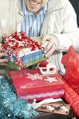 Homem sorridente embrulhar presentes — Fotografia Stock