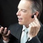 Businessman Using Tablet Adjusting Headset Earpiece. — Stock Photo #31513503