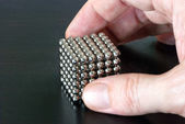 Hand Picking Up Cube of Magnetic Balls — Stock Photo