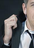 Businessman Wearing Headphones Straightens Jacket — Stock Photo
