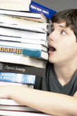 Terrified Teen Looks Up At A Stack Of Textbooks — Stock Photo