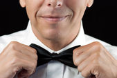 Man In Tux Straightens Bowtie, Two Hands — Stock Photo