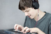 Headphone Wearing Teen Plays Keyboard — Stock Photo