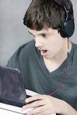 Hoofdtelefoon dragen tiener kijkt naar computer in schok — Stockfoto