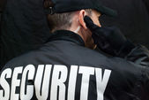 Security Guard Listens To Earpiece, Back of Jacket Showing — Stock Photo