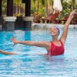 Synchronized female swimmer stretching at the pool — Stock Photo