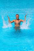 Young beautiful woman splashing water in swimming pool — Stock Photo