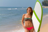 Beautiful sexy young woman surfer girl in bikini with white surfboard on a beach — Stock Photo