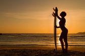 美丽性感的年轻女子冲浪女孩与白色冲浪板比基尼在日落或日出海滩上的后视图 — 图库照片