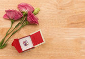 Gift with red flower on wooden vintage table with copy space — Stockfoto