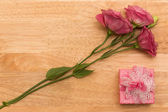 Gift with red flower on wooden vintage table with copy space — ストック写真