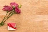 Gift with red flower on wooden vintage table with copy space — Stok fotoğraf