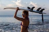 Vrouw surfer met surfboard op tropisch strand bij zonsondergang — Stockfoto