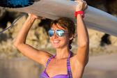 Widok z tyłu piękne sexy kobieta młody internauta dziewczyny w bikini z biały deska surfingowa na plaży na zachód lub wschód słońca — Zdjęcie stockowe