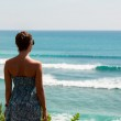 Beautiful woman standing on the edge of the rock and looking for surfers — Stock Photo