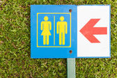Guide post arrow to restroom for men and women on grass — Stock Photo
