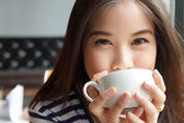 Close up portrait of woman drinking coffee — Stock Photo