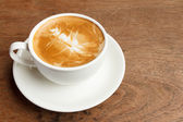 Cup of cappuccino on wooden table  — Stock Photo