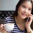 Beautiful woman talking on the phone and  holding cup of coffee — Stock Photo #51042703