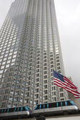 US flag waving against building and grey sky — Stock Photo