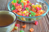 Piala with tea and a glass dish with candied fruit — Stock Photo