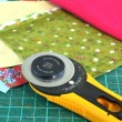 Постер, плакат: Rotary knife and pieces of cloth for patchwork