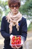 A man carry fresh red strawberry in box — Stock Photo