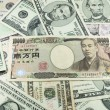 Japanese yen notes on many dollars background — Stock Photo