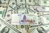 Hundred Cambodian Riel (KHR) on many dollars background — Stock Photo