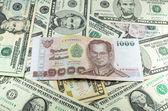 One thousand thai baht (THB) on many dollars background — Stock Photo