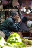 Bagan, myanmar-jan 4: ein nicht identifiziertes birmanischen mann raucht eine zigarre cheroot im markt zu bagan, myanmar am 4 januar, 2011.a cheroot-ist eine zigarre, die hauptsächlich von getrockneten früchten und wenig tabak — Stockfoto