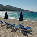 Deck chairs on empty beach — Stock Photo