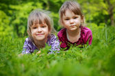 Two young smiling girls in the grass — Foto de Stock