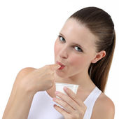 Nice girl eating yogurt sucking finger — Stock Photo
