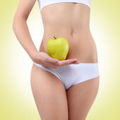 Woman holding an apple with his hands near the belly — Foto de Stock