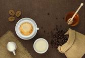 Cup of coffee on the table with beans, sugar, towel, bag, honey and milk — Stock Photo