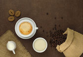 Cup of coffee on the table with beans, sugar, towel, bag and milk — Stock Photo
