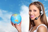 Receptionist with headphones and globe — Stock Photo