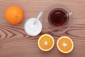 Glass cup of tea with sugar and orange on the table  — Stock Photo