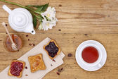 Breakfast table with tea, teapot, cup of tea, jam, bread and hon — Stock Photo