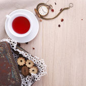 Wooden table for breakfast with cup of tea and biscuits and watc — Foto Stock