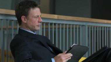 Zakenman gebruiken de Tablet PC- en mobiele telefoon op een zakenreis — Stockvideo